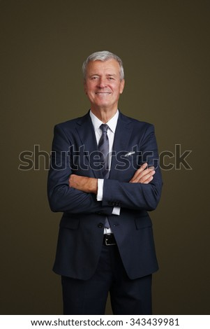 Portrait of financial manager with arms crossed standing at isolated background while looking at camera and smiling.