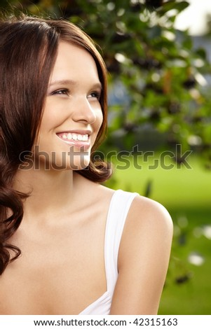 Portrait of fine young woman with curly hair against a summer garden - stock photo