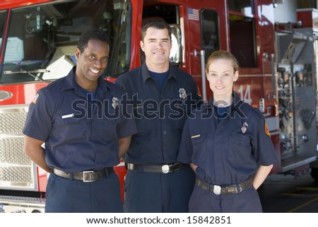 Portrait of firefighters standing by a fire engine