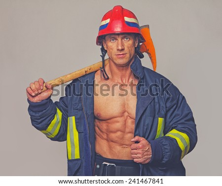 Portrait of fireman on grey background  - stock photo