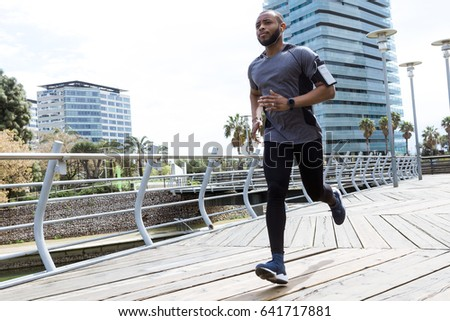 Portrait of fit and sporty young man running in the city.