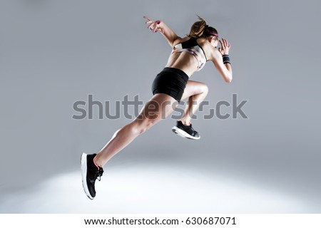 Portrait of fit and sporty young woman running on white background.
