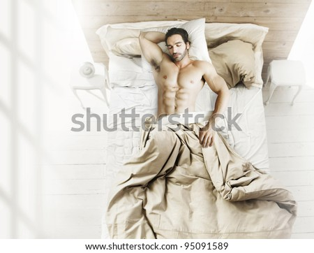 Portrait of fit male model asleep in luxurious bedroom bathed in bright warm morning window light - stock photo