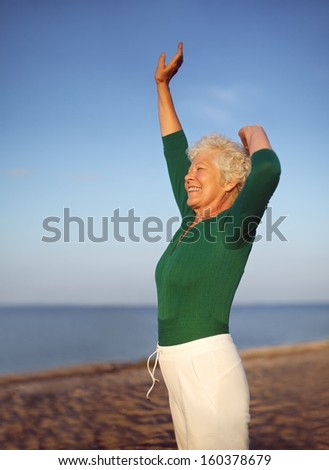 Portrait of fit mature woman practicing yoga on beach with copyspace. Old caucasian woman exercising outdoors to stay fit. Health and fitness concept. - stock photo