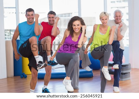 Portrait of fit people performing aerobics exercise in gym class - stock photo