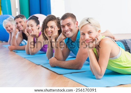Portrait of fit people relaxing on exercise mats at fitness studio - stock photo