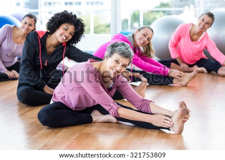 Portrait of fit women smiling while exercising in fitness studio - stock photo