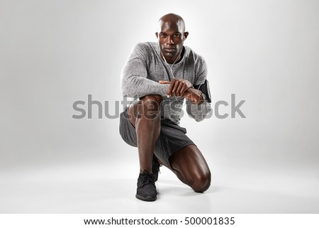 Portrait of fit young african man kneeling on grey background and looking at camera.