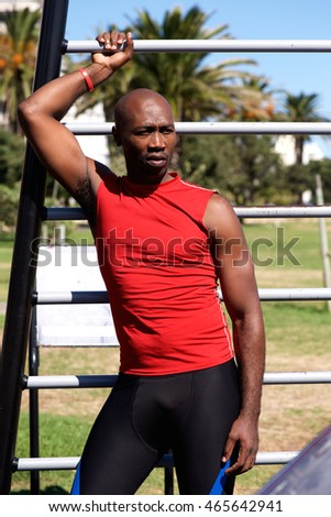 Portrait of fit young african sportsman standing near exercise equipment in the public park