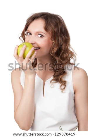 Portrait of fit young girl biting a fresh ripe apple against white background - stock photo