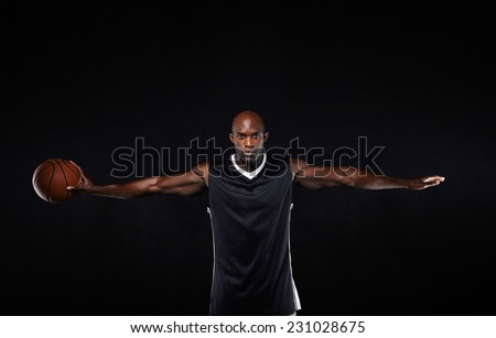 Portrait of fit young man in sportswear holding a basketball standing with his arms outstretched against black background. - stock photo