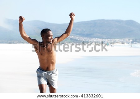 Portrait of fit young man running on the beach with arms raised in victory - stock photo