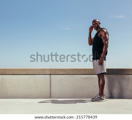 Portrait of fit young man standing on a walkway looking at camera. African fitness model wearing earphones.  - stock photo
