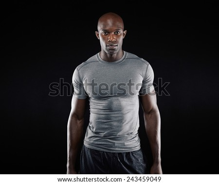 Portrait of fit young man with muscular build standing against black background. Afro american fitness model. - stock photo