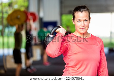 Portrait of fit young woman lifting kettlebell at gym - stock photo