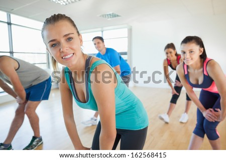 Portrait of fitness class and instructor doing power fitness exercise in fitness studio - stock photo