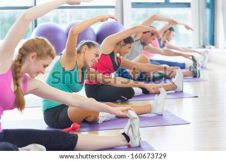 Portrait of fitness class and instructor doing stretching exercise on yoga mats - stock photo