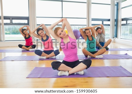 Portrait of fitness class and instructor sitting on yoga mats and stretching hands - stock photo