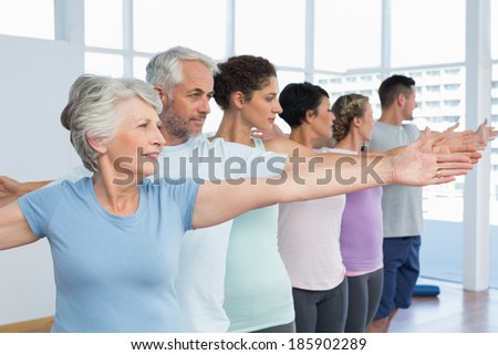 Portrait of fitness class stretching hands in row at yoga class