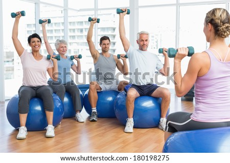 Portrait of fitness class with dumbbells sitting on exercise balls in a bright gym