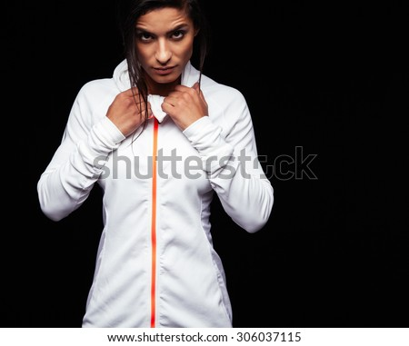 Portrait of fitness woman in sports clothing looking at camera with an attitude. Caucasian female model in sportswear posing against black background with copyspace. - stock photo
