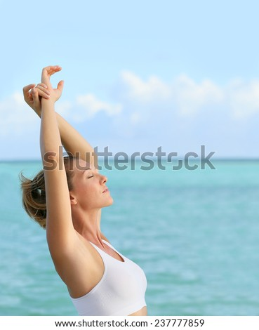 Portrait of fitness woman stretching out by the sea - stock photo