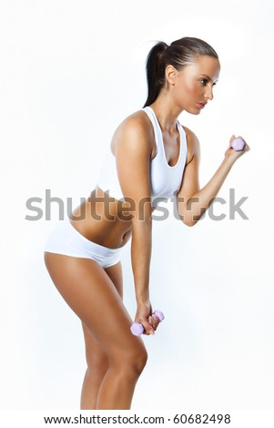 Portrait of fitness woman working out with free weights in gym - stock photo