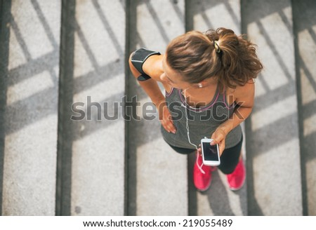 Portrait of fitness young woman with cell phone outdoors in the city - stock photo