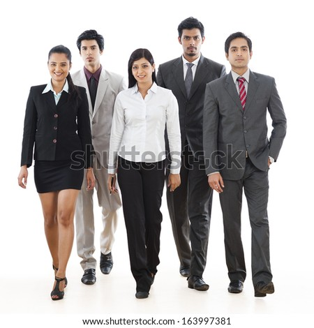 Portrait of five business executives walking - stock photo