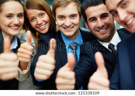 Portrait of five business partners keeping thumbs up and looking at camera with smiles - stock photo