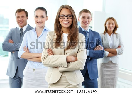 Portrait of five businesspeople looking at camera with female leader in front - stock photo