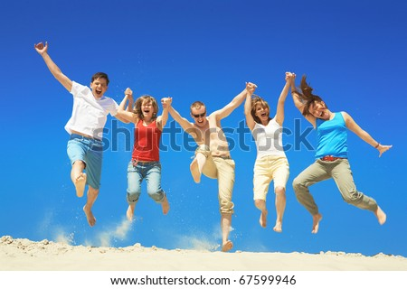 Portrait of five happy people holding by hands and jumping