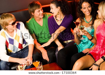 Portrait of five happy people sitting on the sofa and interacting at evening-party
