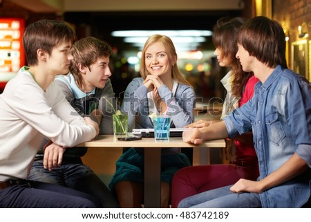 Portrait of five happy students sitting in cafe