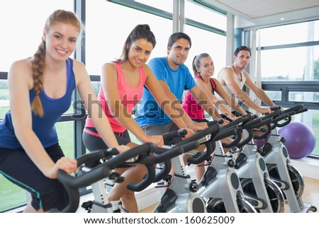 Portrait of five people working out at an exercise bike class in gym