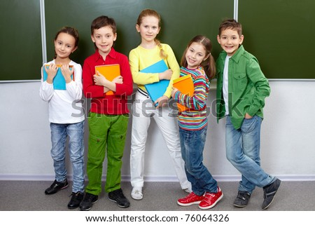 Portrait of five pupils looking at camera in classroom - stock photo
