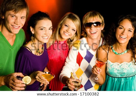 Portrait of five smiling friends with cocktails looking at camera