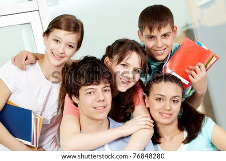 Portrait of five students embracing looking at camera and smiling