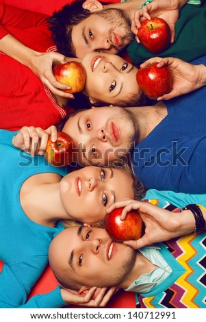 Portrait of five stylish close friends hugging and lying over red background. Guys having fun and holding red apples. Healthy food concept. Hipster style. Studio shot - stock photo