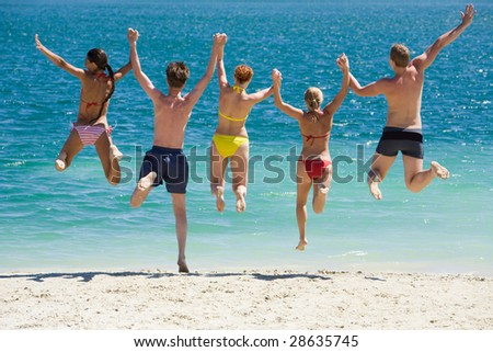 Portrait of five teens jumping into lake simultaneously holding each other by hands - stock photo