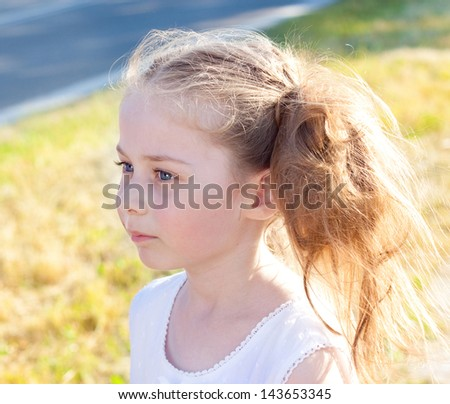 Portrait of five years old blond caucasian child girl standing outdoor by the road at sunset - stock photo