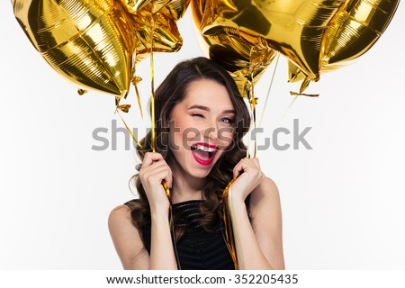Portrait of flirty attractive winking curly retro styled woman with golden balloons - stock photo