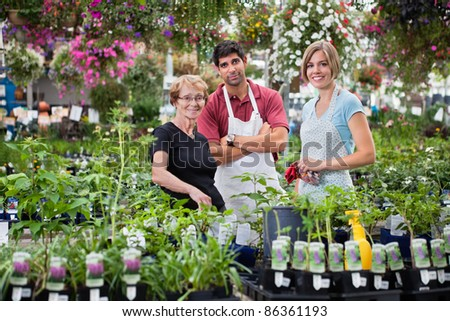 Portrait of florists standing with female customer - stock photo