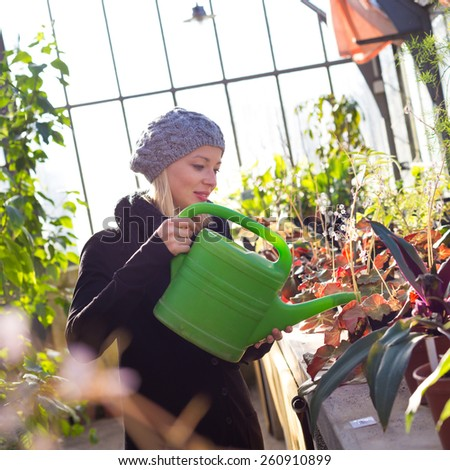 Portrait of florists woman working with flowers in a greenhouse holding a watering can in her hand. Small business owner. - stock photo