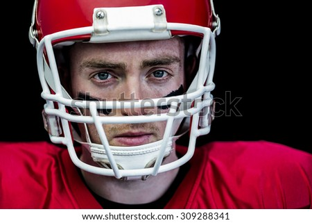 Portrait of focused american football player wearing his helmet against black background - stock photo