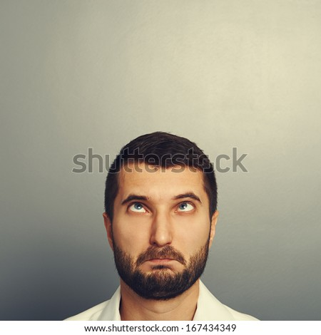 portrait of foolish man over grey background - stock photo