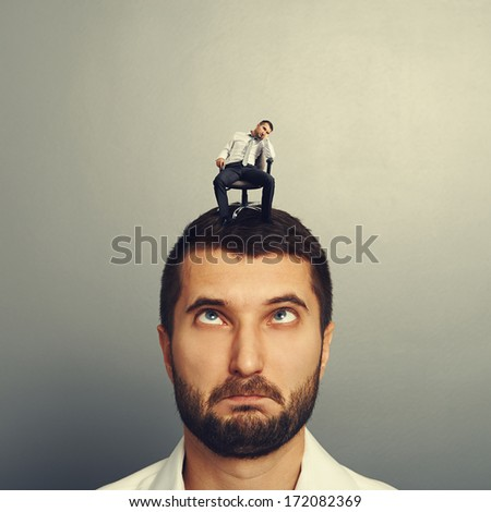portrait of foolish man with small bored man on the head - stock photo
