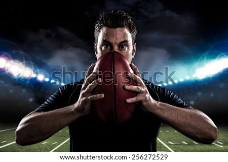 Portrait of football player holding a ball - stock photo