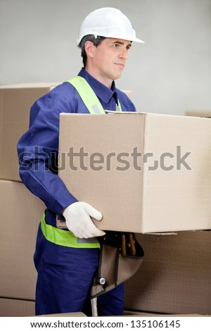 Portrait of foreman lifting cardboard box at warehouse - stock photo