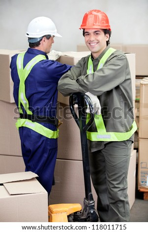 Portrait of foreman with colleague working at warehouse - stock photo